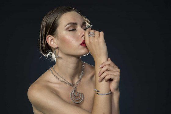 Frau mit Diamantkette mit großem Anhänger, Diamantohrringen, Armband und Ring.